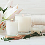 Two white candles burning next to towels and flowers