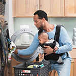 Man holding baby putting laundry in a washing machine