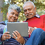 Older couple smiling while looking at a digital tablet together