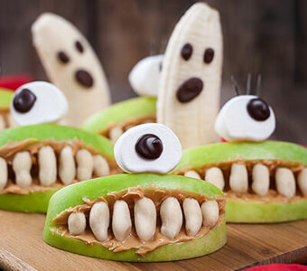 Halloween themed healthy snacks with bananas, apples and peanut butter