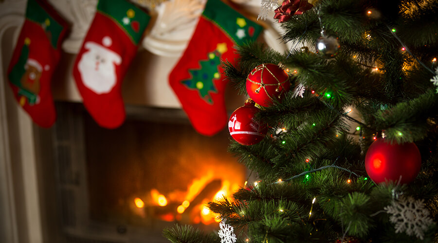 Closeup of ornaments on a Christmas tree in front of a fireplace with stockings hanging from its mantle