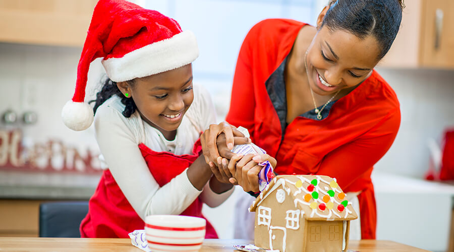 Mother and child putting icing on a gingerbread house