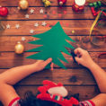 Child using scissors to cut a green tree from construction paper