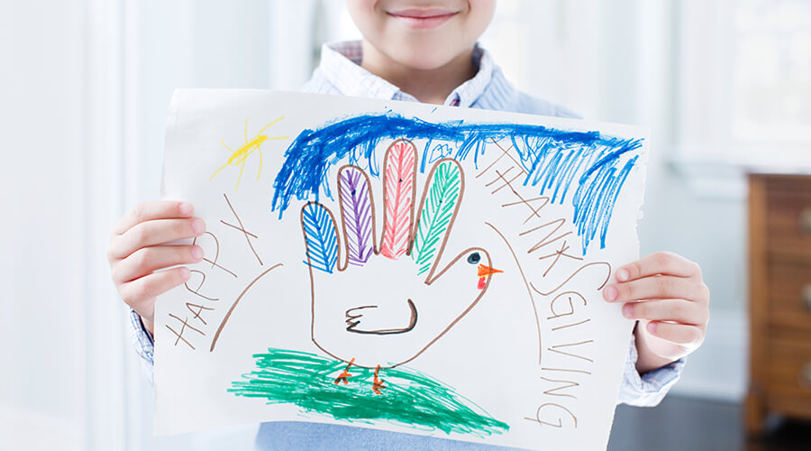 Child holding a drawing of a turkey that says Happy Thanksgiving