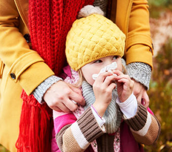 Child blowing their nose with a facial tissue while standing outside in front of an adult