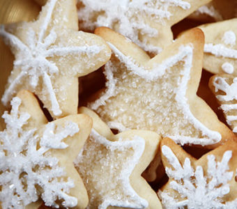 Closeup of sugar cookies in snowflake shapes with white frosting