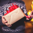 Closeup of person holding a wrapped gift with a ribbon on top