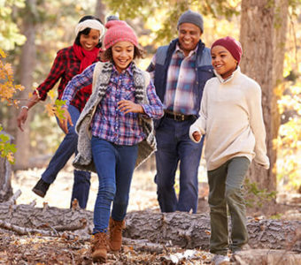 Family hiking on wooded path in the fall