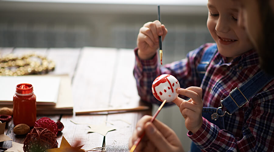 Child painting a white ornament