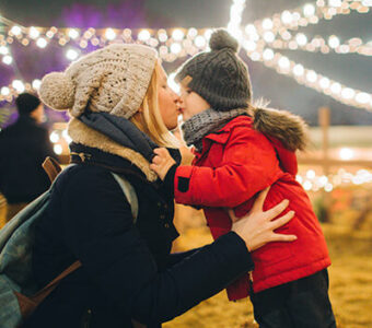 Mother and child kissing under holiday lights
