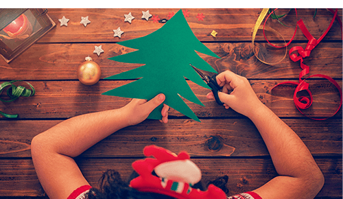 Child cutting out craft paper into the shape of a tree