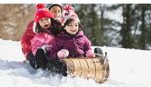 Children on sled going down snow covered hill