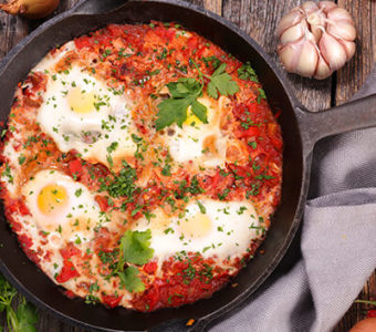 Cast iron pan filled with shakshuka and eggs