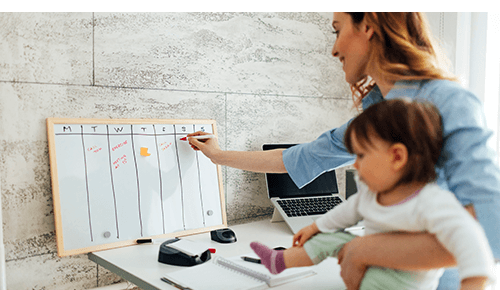 Woman holding infant while writing on a whiteboard with days of the week written on it