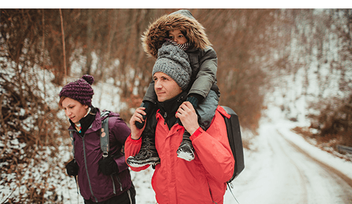 Parents and child wearing cold weather gear and walking on a snow covered path