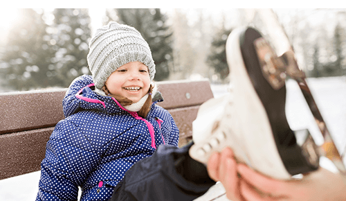 Young child smiling while an adult puts an ice skate on their foot
