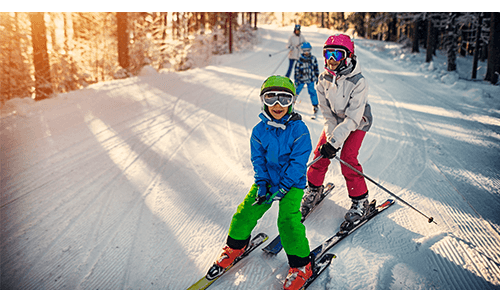 Children skiing together on snow covered hill