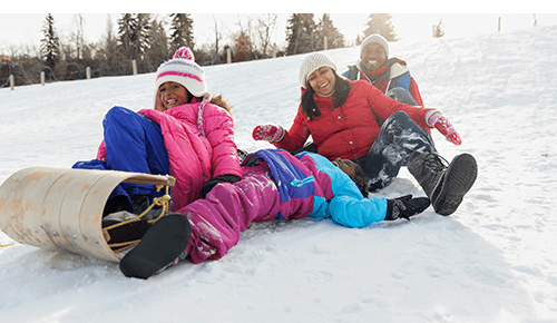 Couple and two children sitting on sled on snow covered hill