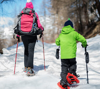 Adult and child walking on snow covered path wearing snow shoes