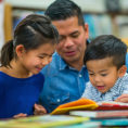 Father and children looking at book together in library