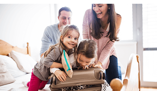 Family with two children packing a suitcase in bedroom
