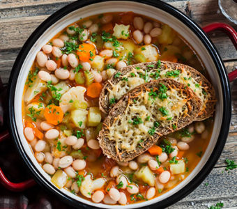 Pot full of vegetable soup with pieces of bread on top