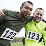 Two people hugging and smiling after running race outdoors
