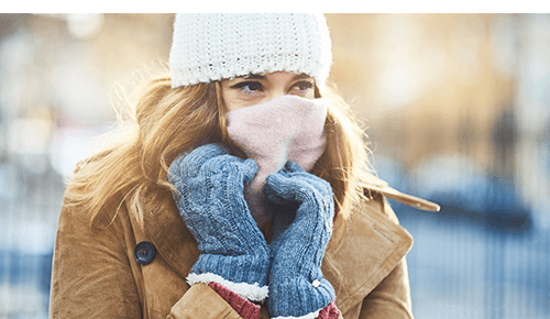 Woman bundled up with scarf and cold winter gear while standing outside