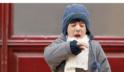 Child sneezing while standing outside with cold winter gear on