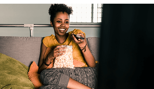 Woman watching tv and snacking on popcorn