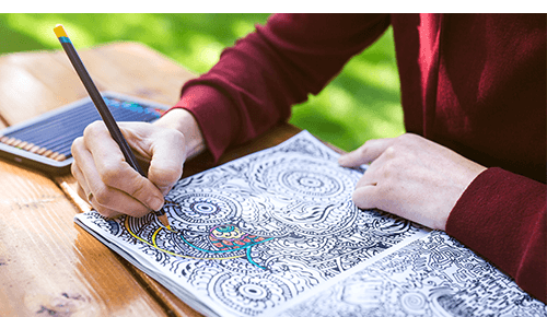 Person coloring in coloring book with colored pencils