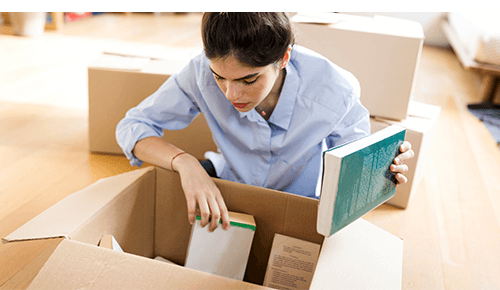 Person looking through moving box of books