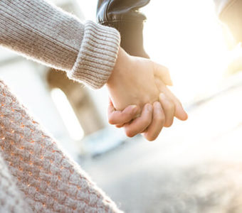 Closeup of two people holding hands while walking down the street