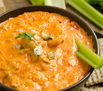 Bowl of buffalo chicken dip with celery sticks and crackers