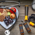 Heart shaped plate with grains, fruits and vegetables sitting next too workout equipment and a stethoscope