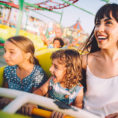 Adult and two children on rollercoaster ride at fair