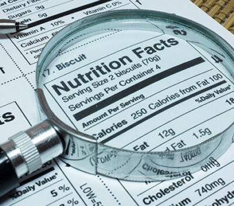 Closeup of nutrition label on food packaging using magnifying glass