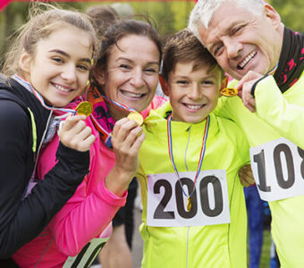 Family holding up medals after running a race