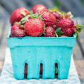 Small blue container of strawberries
