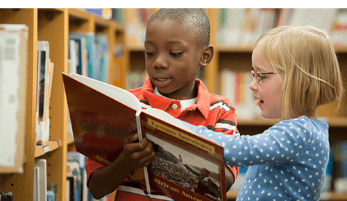 Children at Library Reading Book