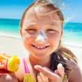 Child smiling into camera while putting sunscreen on their face near the beach