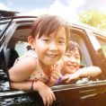 Father and children smiling while looking out car windows