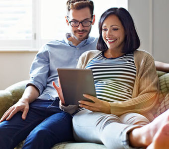 Couple sitting on couch looking at digital tablet together