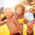 Group of children wearing swimsuits throwing water balloons