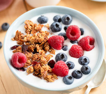 Bowl of yogurt with granola and berries on top