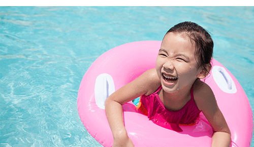 Child in pool floaty laughing