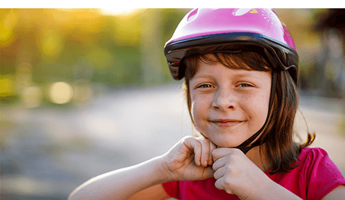 Child putting on their bicycle helmet