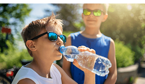 Child drinking from a bottle of water while other child watches in background