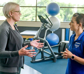 Woman talking to an Exercise Physiologist on a running track in a gym