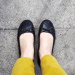 Closeup of person wearing black ballet flats